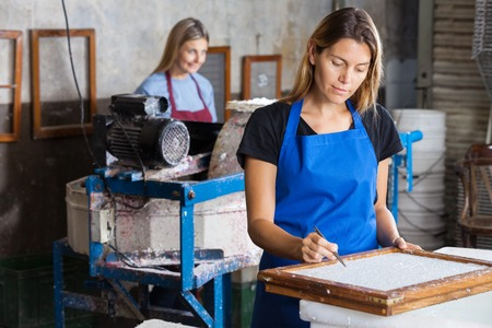 deckle: Female worker using tweezers to clean paper on mold in factory