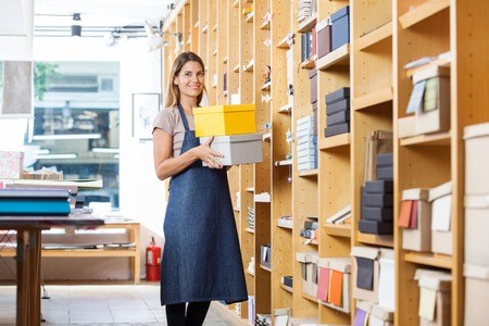 Portrait of confident mid adult woman carrying boxes in store 스톡 콘텐츠