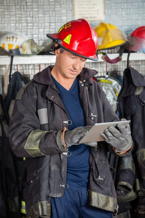 using tablet: Mature male firefighter in uniform using digital tablet at fire station