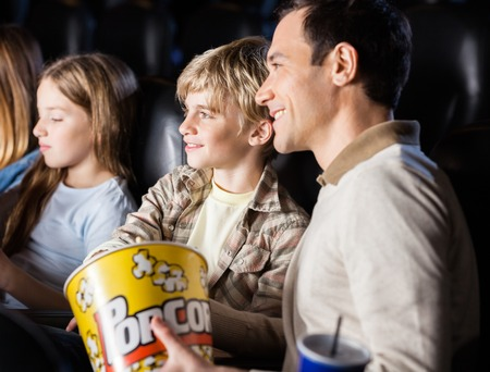 cinema film: Family having popcorn while watching movie in cinema theater