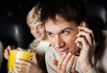 mobilephone: Closeup of mid adult man using mobilephone in cinema theater with son in background Stock Photo