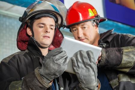 bombero: �ngulo de visi�n baja de los bomberos de sexo masculino que usa la tableta digital con estaci�n de bomberos