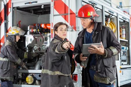 firefighter: Mujer bombero apuntando mientras colega sostiene la tablilla digital con cami�n en la estaci�n de bomberos