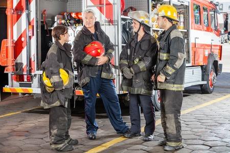 bombera: Retrato de cuerpo entero de bombero masculina confía en pie con equipo contra el camión en la estación de bomberos Foto de archivo