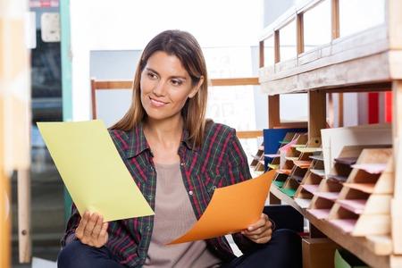 paper craft: Sonriente que elige el cliente femenino entre los papeles amarillos y anaranjados en la tienda