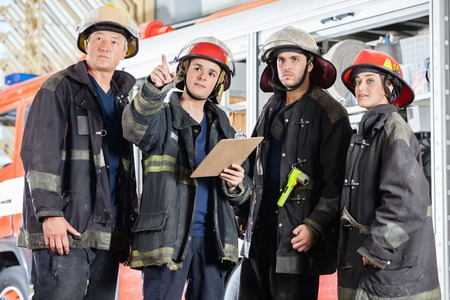 first responder: Confident male firefighter showing something to colleagues at fire station Stock Photo