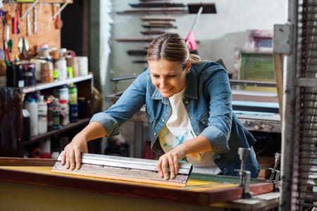 impresión: Sonriente mediados trabajador adulto femenino usando la escobilla de goma en la fábrica