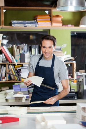 mid adult male: Portrait of smiling mid adult male worker holding papers and ruler at table in paper industry
