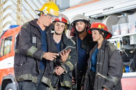 Team van brandweerlieden met behulp van digitale tablet tegen brandweerwagen op station Stockfoto