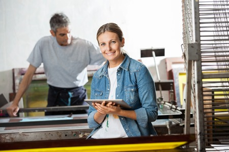 paper factory: Portrait of smiling female worker holding digital tablet while colleague working in background at paper factory
