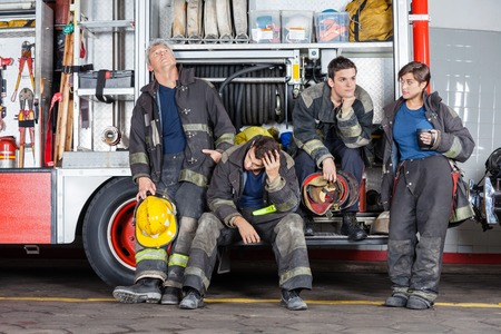 leaning on the truck: Team of tired firefighters at truck in fire station