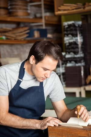 mid adult male: Mid adult male worker using needle to make holes on paper in factory Stock Photo