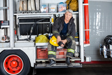 fireman: Full length portrait of confident fireman sitting in truck at fire station