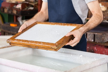 paper factory: Midsection of male worker holding mold over pulp and water mixture at paper factory Stock Photo