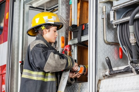 firefighter: Side view of female firefighter fixing water hose in truck at fire station Stock Photo