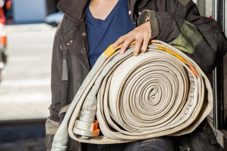 fireman with hose: Midsection of young fireman holding water hose at fire station Stock Photo