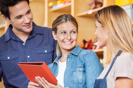 book shop: Happy mid adult couple looking at saleswoman holding book in shop Stock Photo