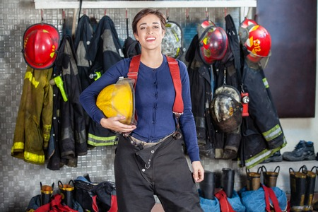 firefighter: Portrait of confident female firefighter holding helmet while standing at fire station