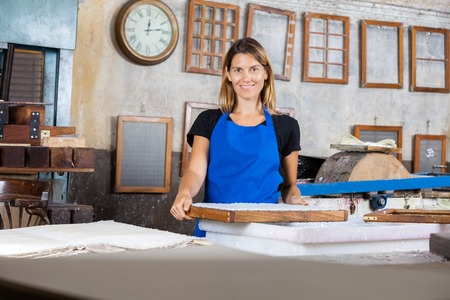 mid adult female: Portrait of smiling mid adult female worker holding mold at paper factory