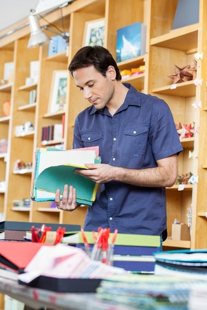 book shop: Mid adult man looking at colorful papers in shop