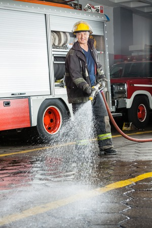 fireman with hose: Portrait of smiling fireman spraying water on floor during training at fire station