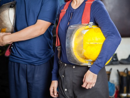 midsection: Midsection of male and female firefighters holding helmets at fire station