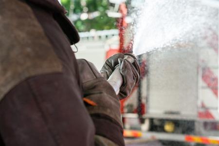 voiture de pompiers: image recadrée de pompier pulvériser de l'eau lors de la pratique à la caserne des pompiers Banque d'images