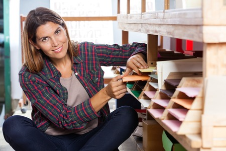 store shelf: Portrait of smiling mid adult female customer choosing papers from shelf in store