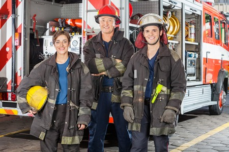 fireman: Portrait of happy firefighters standing together against truck at fire station Stock Photo