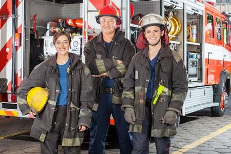 bombero: Retrato de los bomberos felices de pie juntos contra el cami�n en la estaci�n de bomberos Foto de archivo