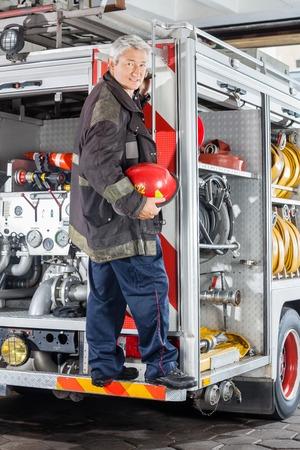 fireman helmet: Full length portrait of smiling fireman standing on truck at fire station