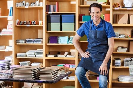 delantal: Retrato de la sonrisa mediados vendedor de adulto que se sienta en la escalera en tienda de libros