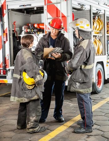 protective: Full length of male and female firefighters discussing over clipboard against truck at fire station