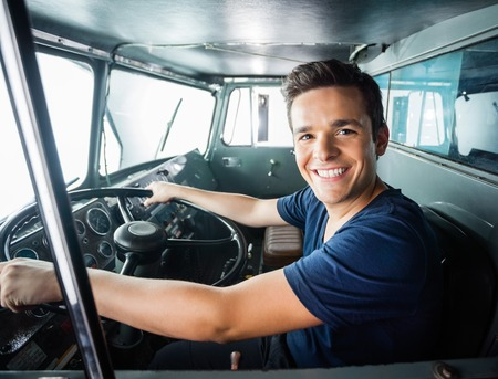 truck engine: Portrait of happy young fireman driving firetruck at station Stock Photo