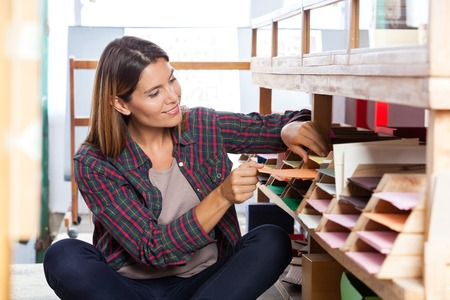 mid adult female: Smiling mid adult female customer choosing paper from shelf in store Stock Photo