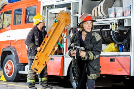 firefighter: Alert male firefighter holding hose while colleague carrying wooden stretcher by truck at fire station