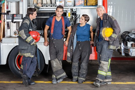 leaning on the truck: Full length of confident firefighters leaning on truck at fire station Stock Photo