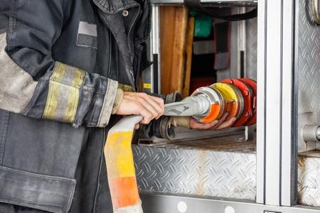 firefighter: Secci�n media de bombero masculina ajustar la manguera en el cami�n en la estaci�n de bomberos Foto de archivo