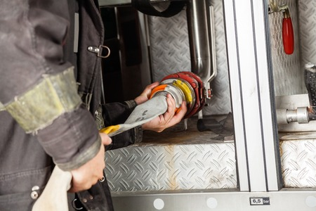 fireman with hose: Midsection of mature fireman adjusting water hose in truck at fire station Stock Photo