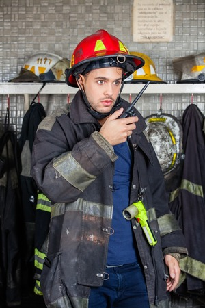 walkie: Young male firefighter looking away while using walkie talkie at fire station