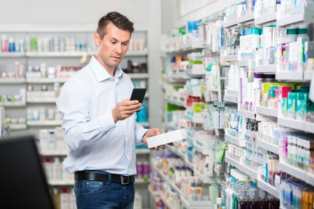 Metà dei consumatori maschio adulto verifica di informazioni sul telefono cellulare mentre si tiene prodotto in farmacia Archivio Fotografico - 43960019