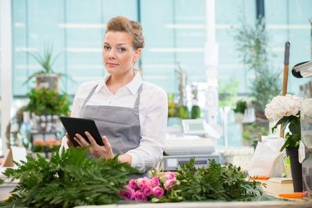 Portrait of female florist using digital tablet at counter in flower shop