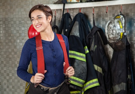 female worker: Smiling female firefighter looking away while standing at fire station