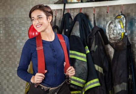 bombera: Sonreír bombero de sexo femenino que mira lejos mientras está de pie en la estación de bomberos Foto de archivo