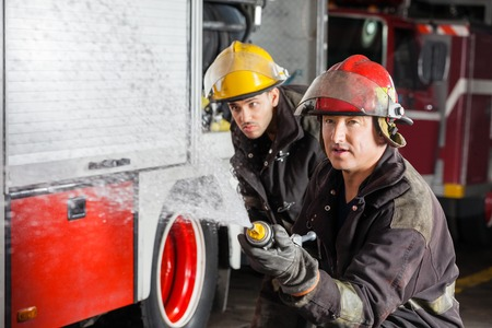 fireman: Confident young and mature firemen spraying water during training at fire station