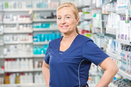 various occupations: Portrait of smiling female chemist standing in pharmacy