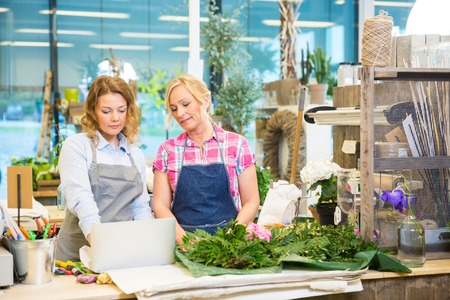 associates: Female florists using laptop on counter in flower shop Stock Photo