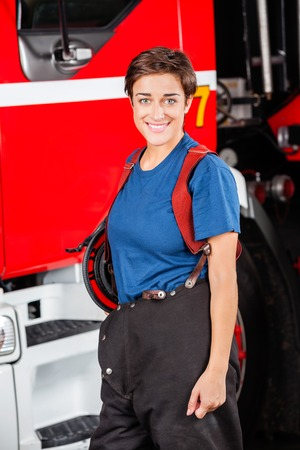firetruck: Portrait of happy female firefighter standing against firetruck at station