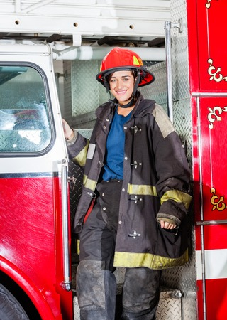 female driver: Portrait of happy female firefighter in uniform standing on truck at fire station