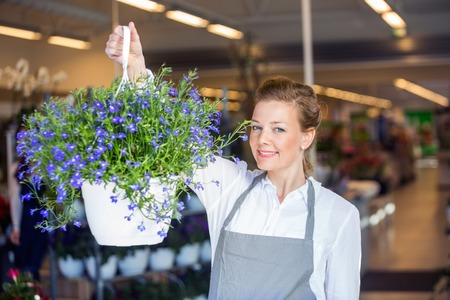 mid adult   female: Portrait of beautiful mid adult female florist holding flower plant in shop Stock Photo
